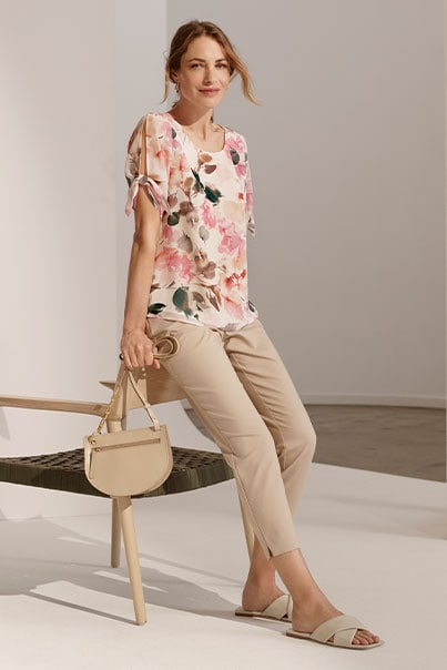 Woman in floral print blouse and tan pants