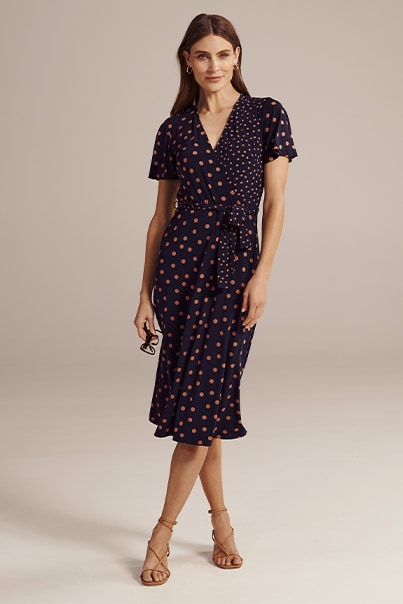 Woman in navy spot print dress