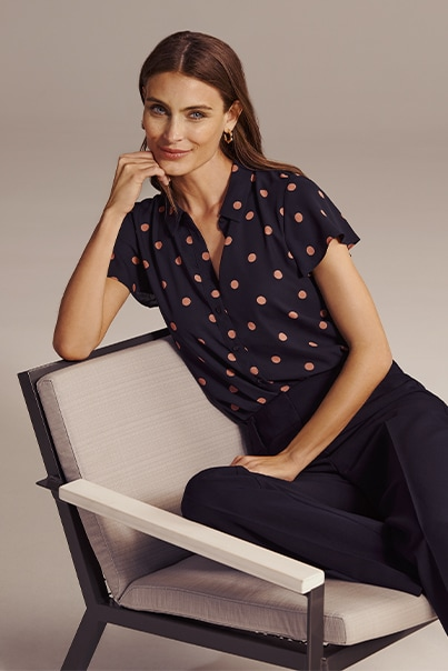 Woman in navy spot print blouse and navy pants