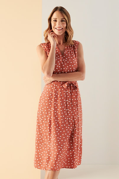 Woman in orange spot print dress