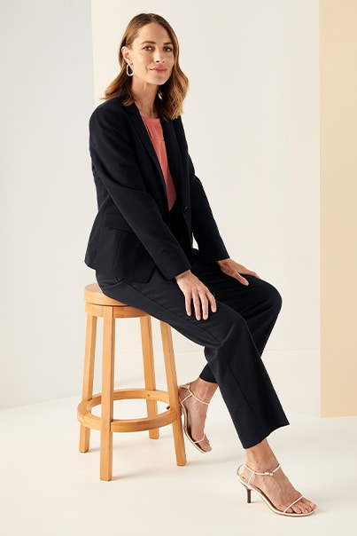 Woman in navy jacket, orange blouse and navy pants